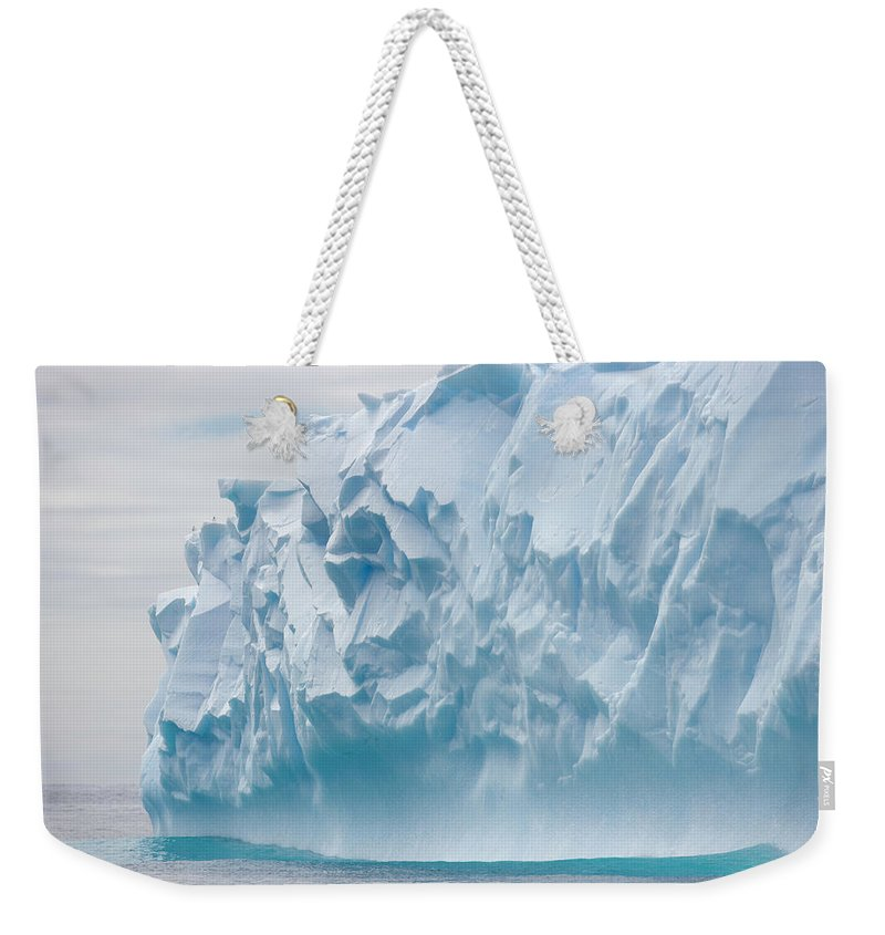 Scenics Weekender Tote Bag featuring the photograph Blue Iceberg Carved By Waves Floats In by Eastcott Momatiuk