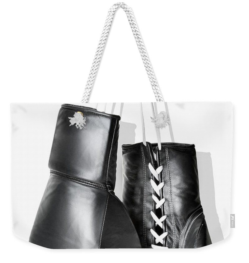 Hanging Weekender Tote Bag featuring the photograph Boxing Gloves Hanging Against White by Burazin