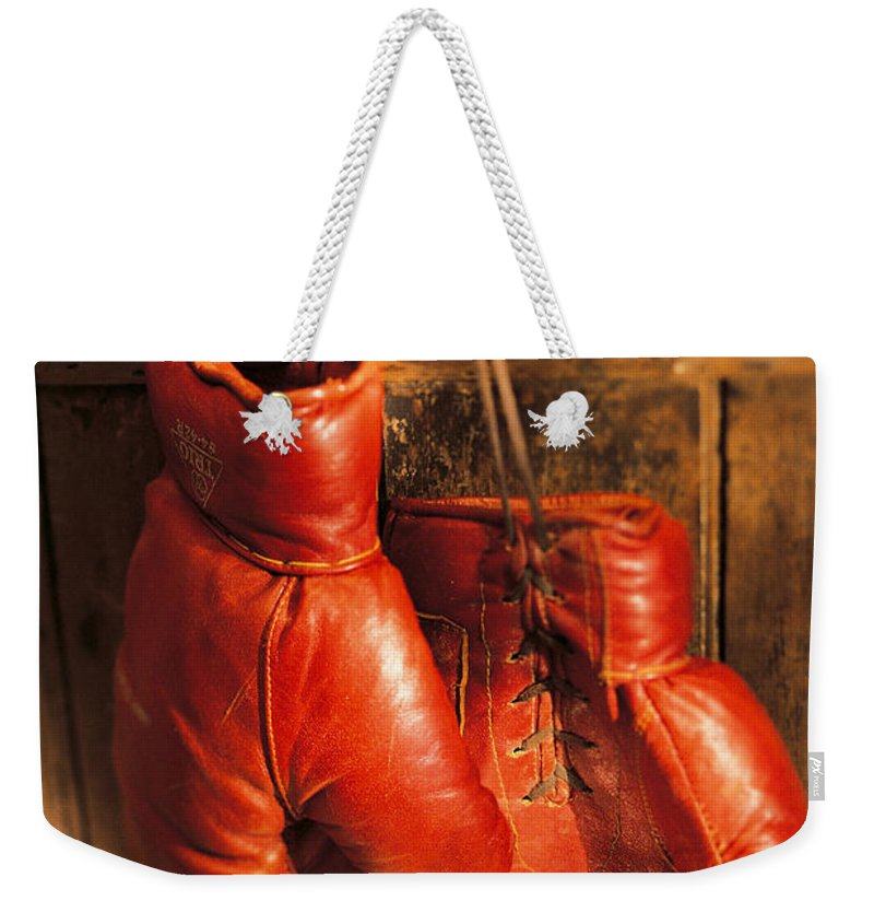Hanging Weekender Tote Bag featuring the photograph Boxing Gloves Hanging On Rustic Wooden by Comstock
