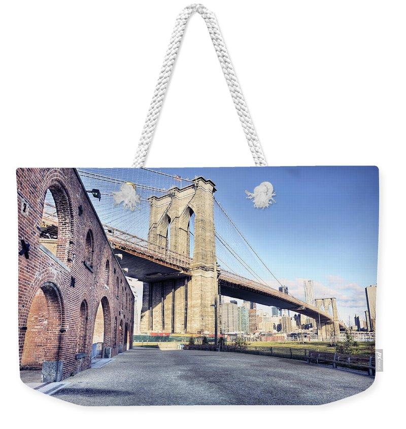 Lower Manhattan Weekender Tote Bag featuring the photograph Brooklyn Bridge From Down Under by By Gene Krasko