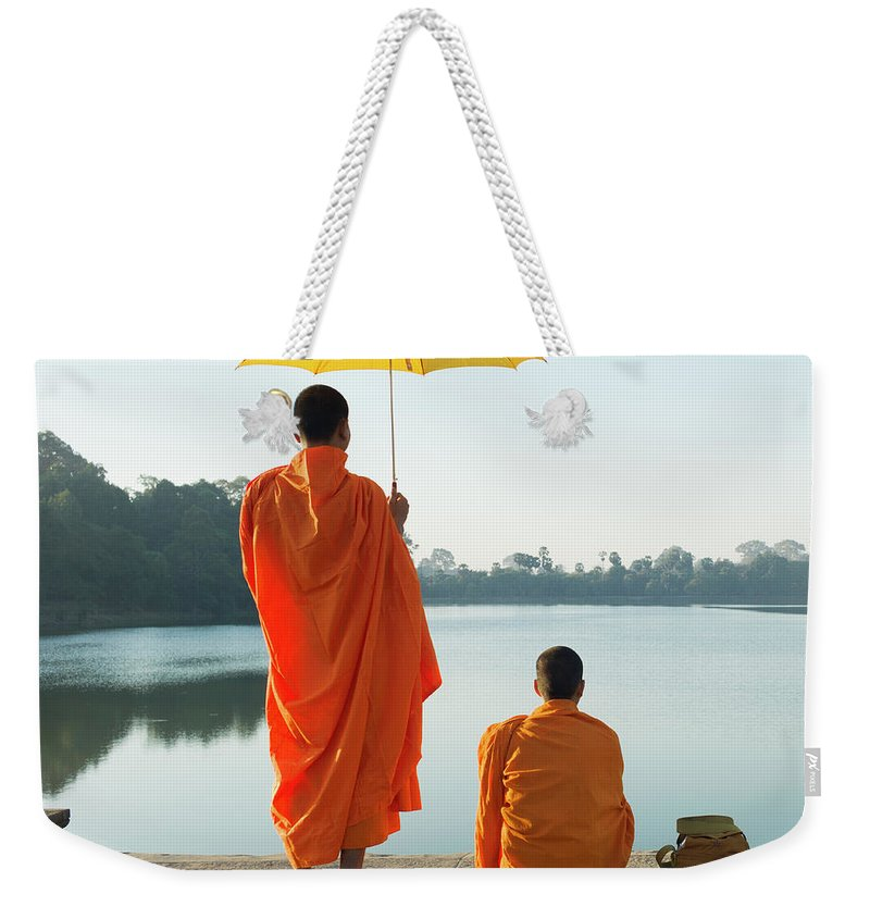 Young Men Weekender Tote Bag featuring the photograph Buddhist Monks Standing In Front Of by Martin Puddy