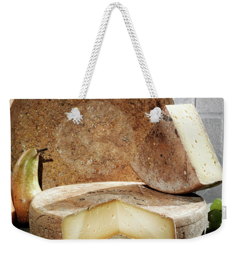 Fontina Weekender Tote Bag featuring the photograph Cheese, Fruit And Grains On Table by Walter Zerla