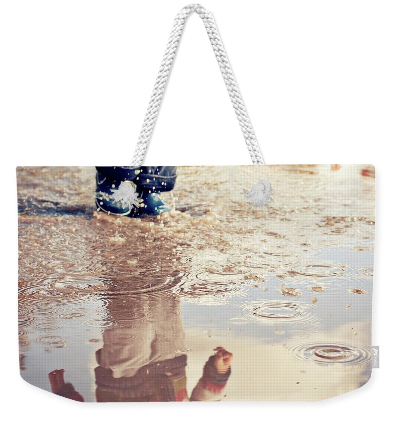 Toddler Weekender Tote Bag featuring the photograph Child In A Puddle by Vpopovic