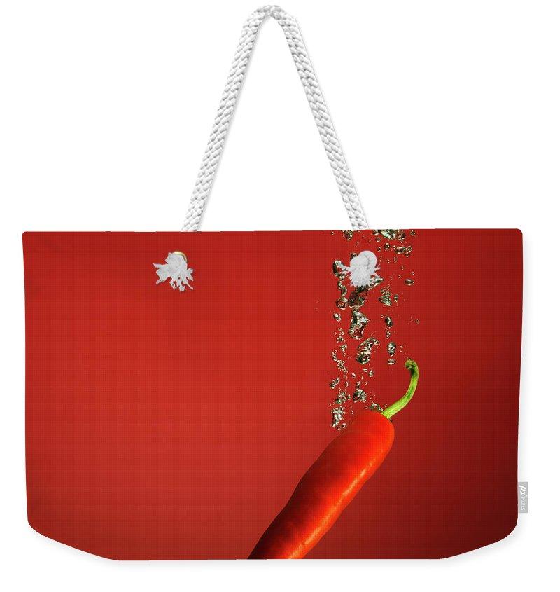 Copenhagen Weekender Tote Bag featuring the photograph Chilli Splashed Into Water by Henrik Sorensen