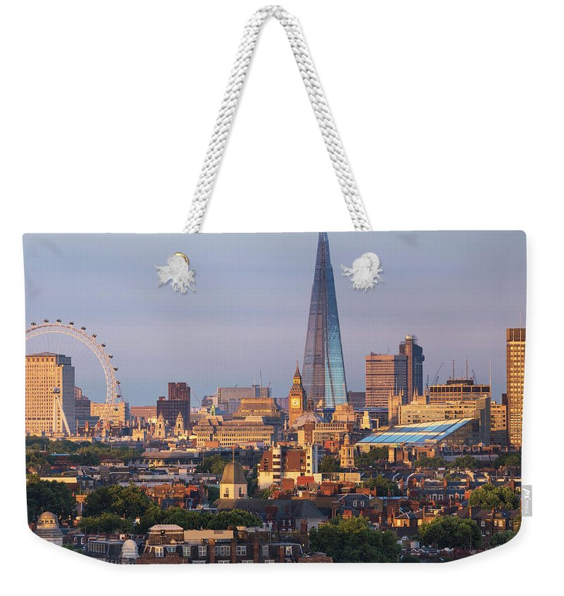 Tranquility Weekender Tote Bag featuring the photograph City Skyline In Late Evening Sunlight by Simon Butterworth