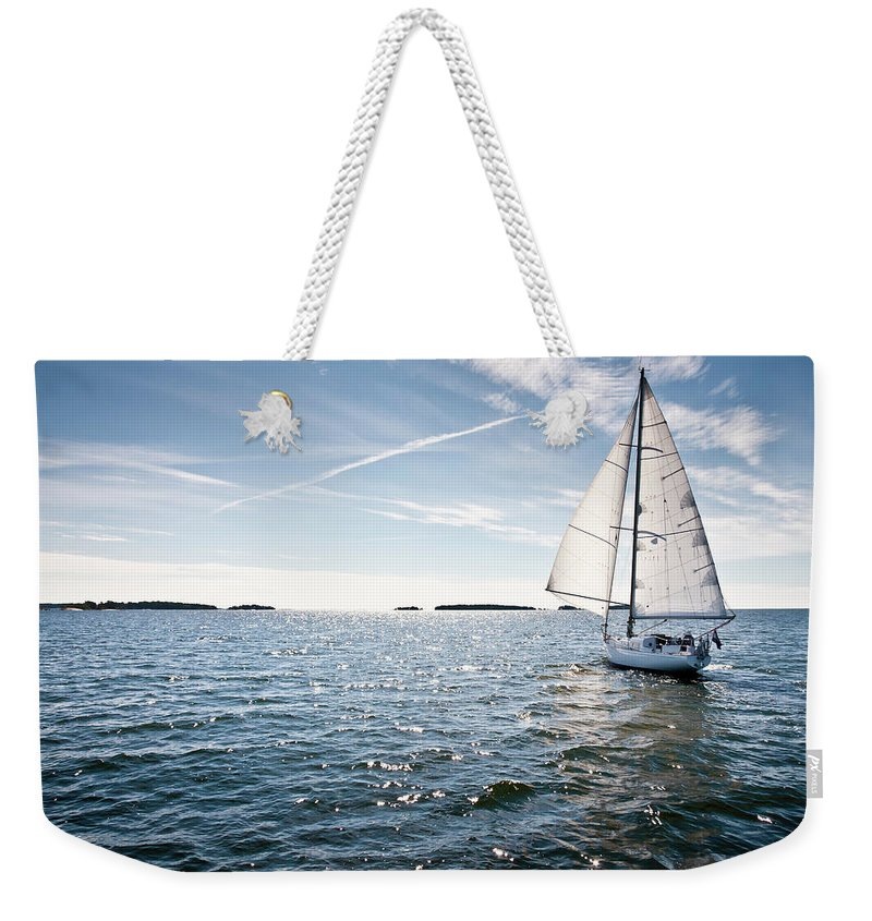 Recreational Pursuit Weekender Tote Bag featuring the photograph Classic Yacht Sailing Away Against Blue by Jaap-willem