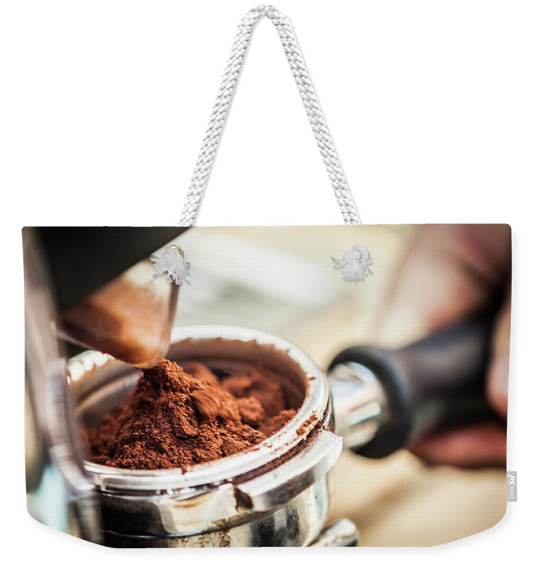 Mature Adult Weekender Tote Bag featuring the photograph Close Up Of Espresso Grounds In Machine by Manuel Sulzer