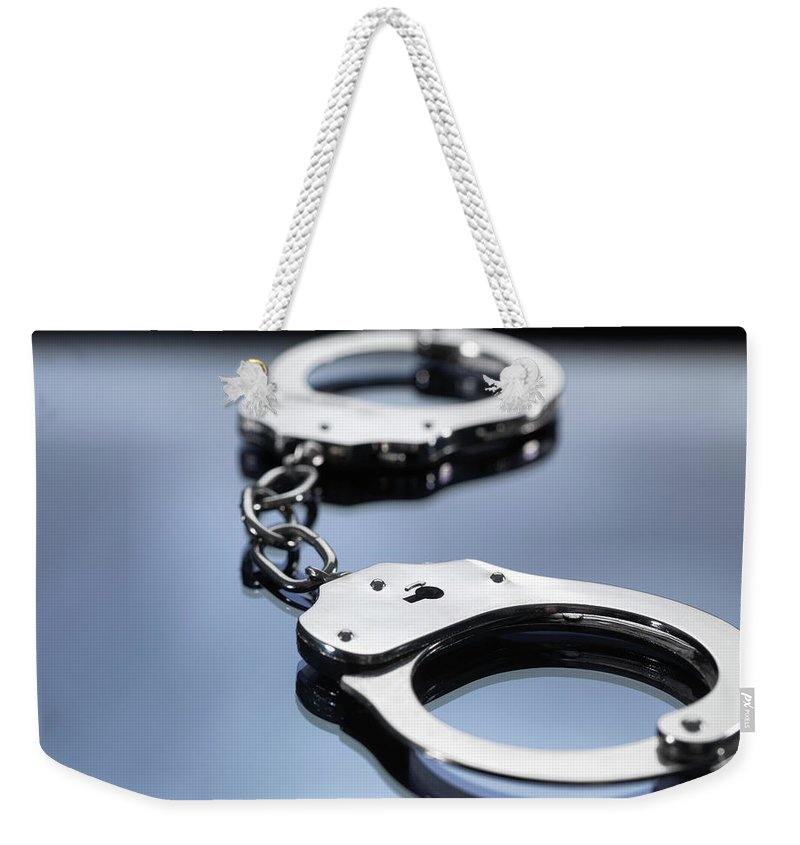 Punishment Weekender Tote Bag featuring the photograph Close Up Of Metal Handcuffs by Andrew Brookes