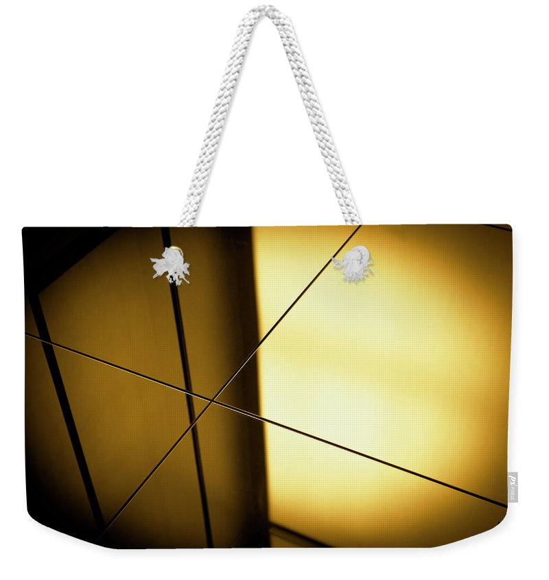 Shadow Weekender Tote Bag featuring the photograph Close-up Spot Lit Reflection In Yellow by Ralf Hiemisch