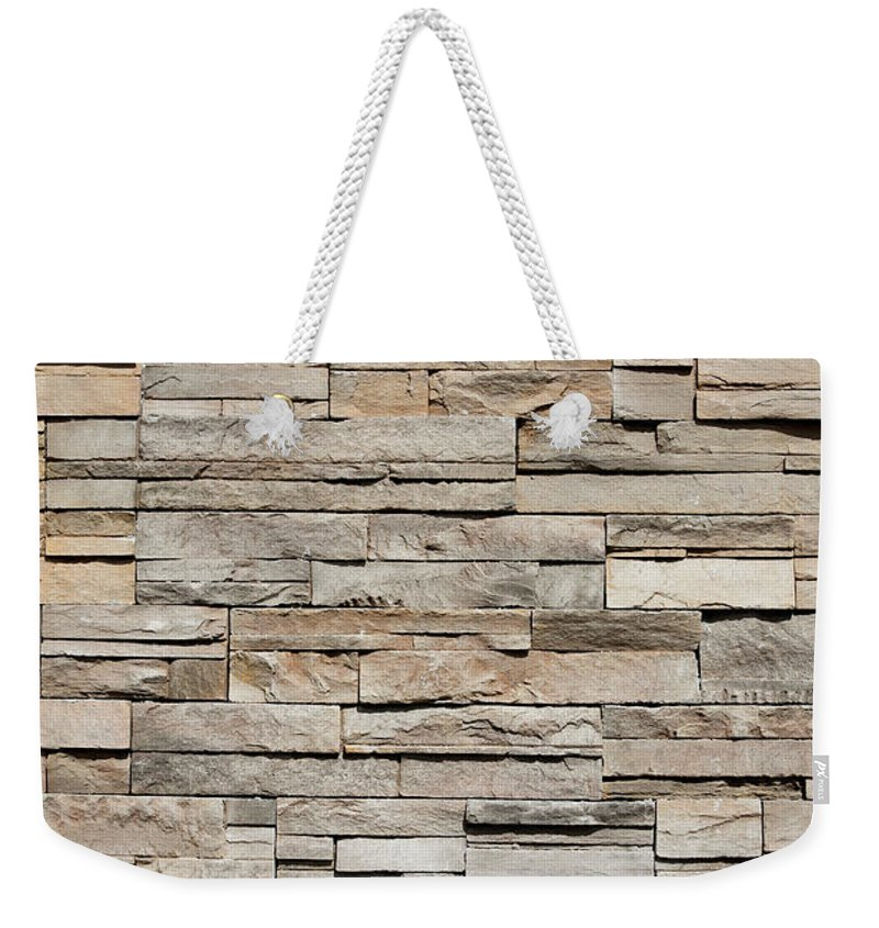 Rectangle Weekender Tote Bag featuring the photograph Closeup Of A Sandstone Brick Side Of by Carterdayne