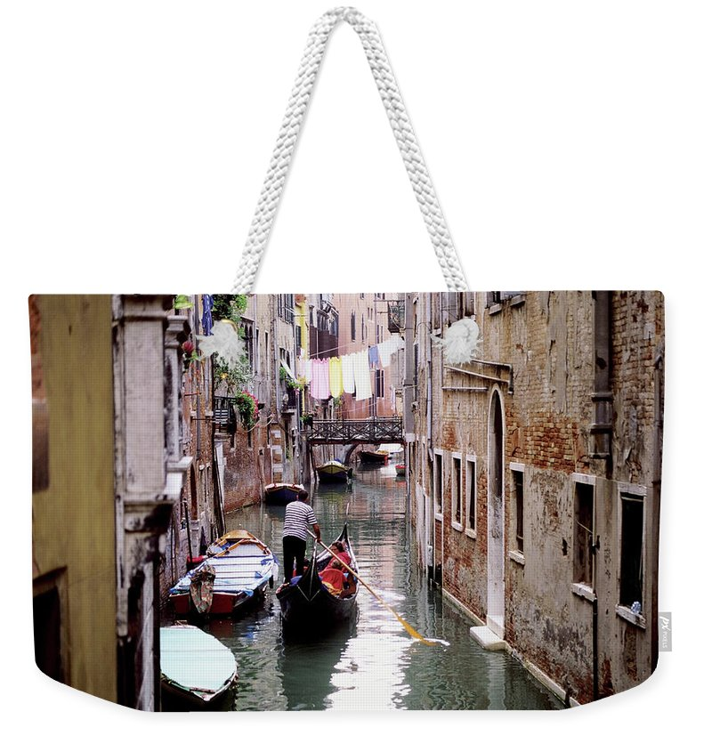 Hanging Weekender Tote Bag featuring the photograph Clothes Hanging Over Ghetto Canal by Medioimages/photodisc