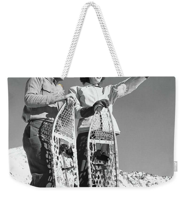 Heterosexual Couple Weekender Tote Bag featuring the photograph Couple Holding Snowshoes, Woman Pointing by Stockbyte
