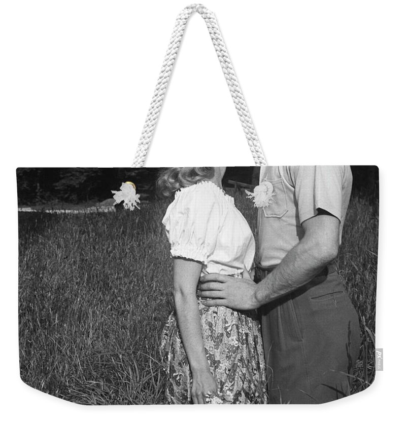 Heterosexual Couple Weekender Tote Bag featuring the photograph Couple Kissing Outdoors by George Marks