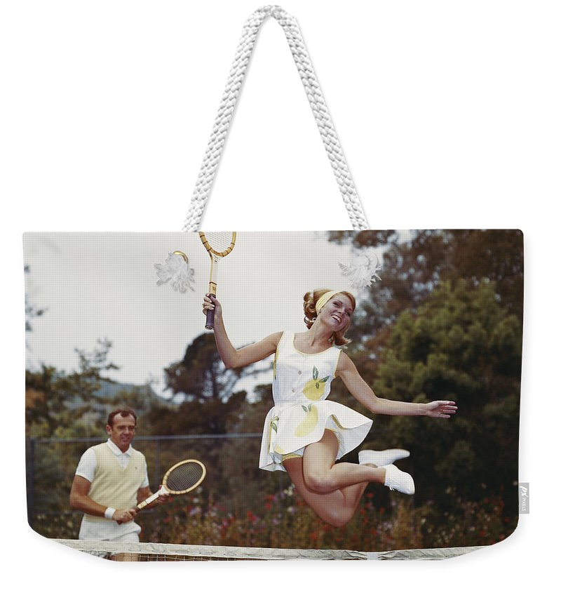 Heterosexual Couple Weekender Tote Bag featuring the photograph Couple On Tennis Court, Woman Jumping by Tom Kelley Archive