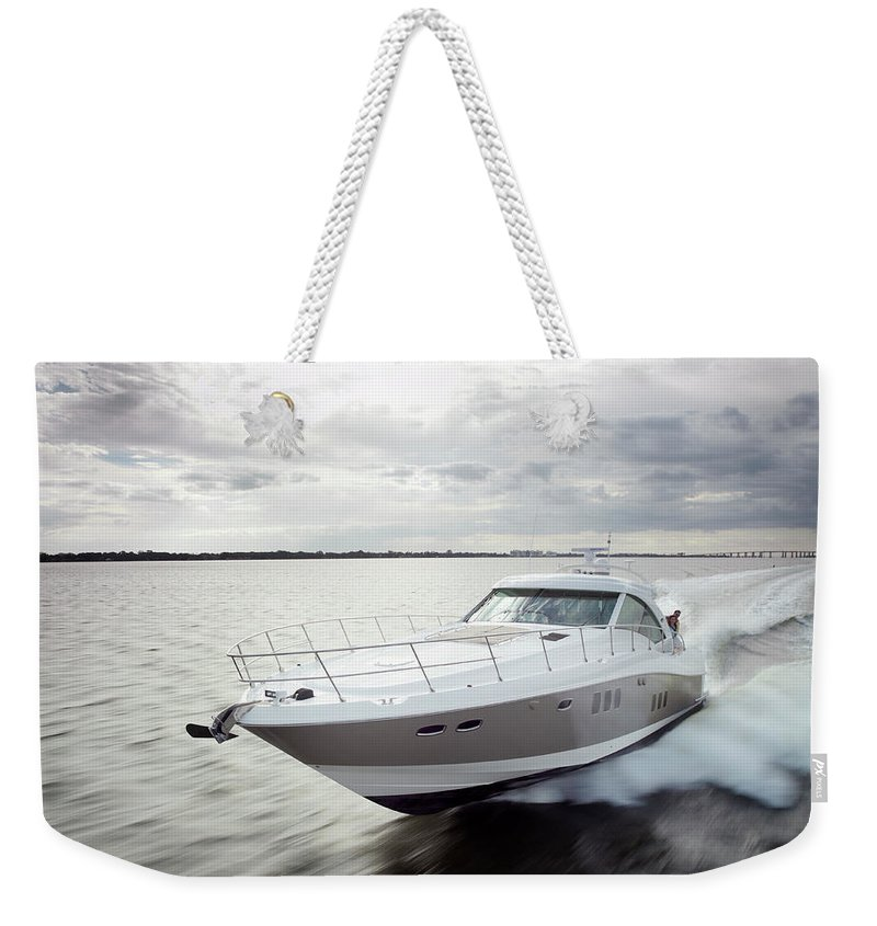 Wake Weekender Tote Bag featuring the photograph Couple Relaxing On Speed Boat, Dawn by Gary John Norman
