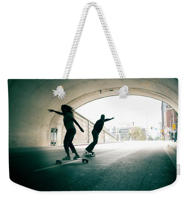 Mature Adult Weekender Tote Bag featuring the photograph Couple Skateboarding Through Tunnel by Ian Logan
