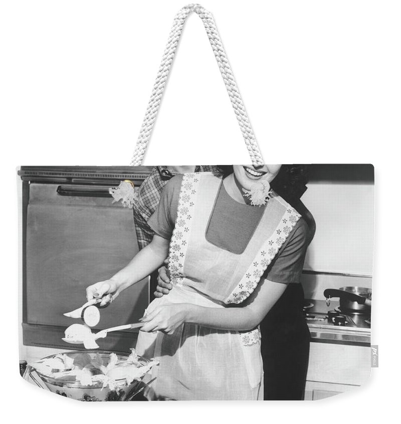 Heterosexual Couple Weekender Tote Bag featuring the photograph Couple Standing In Kitchen, Smiling, B&w by George Marks