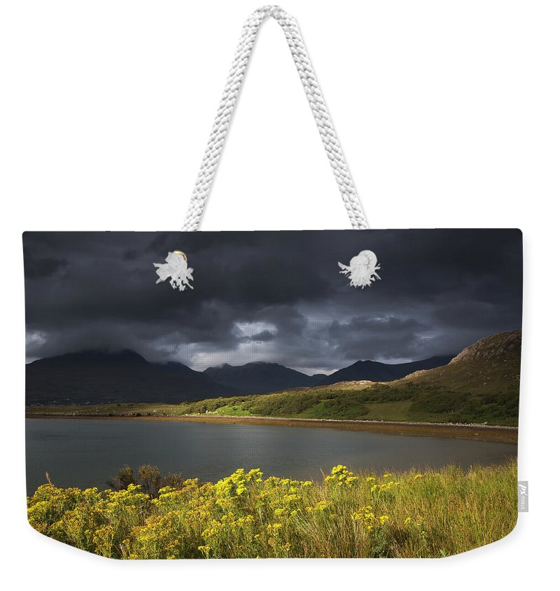 Tranquility Weekender Tote Bag featuring the photograph Dark Storm Clouds Hang Over The by John Short / Design Pics