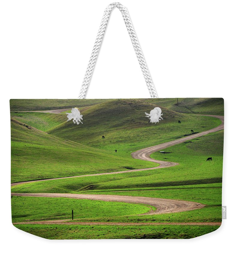 Tranquility Weekender Tote Bag featuring the photograph Dirt Road Through Green Hills by Mitch Diamond