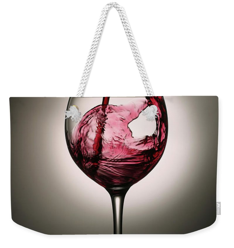 Alcohol Weekender Tote Bag featuring the photograph Dramatic Red Wine Splash Into Wine Glass by Donald gruener