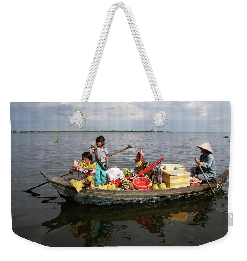 Child Weekender Tote Bag featuring the photograph Family & Snake Sell Wares On Tonle by Rosemary Calvert
