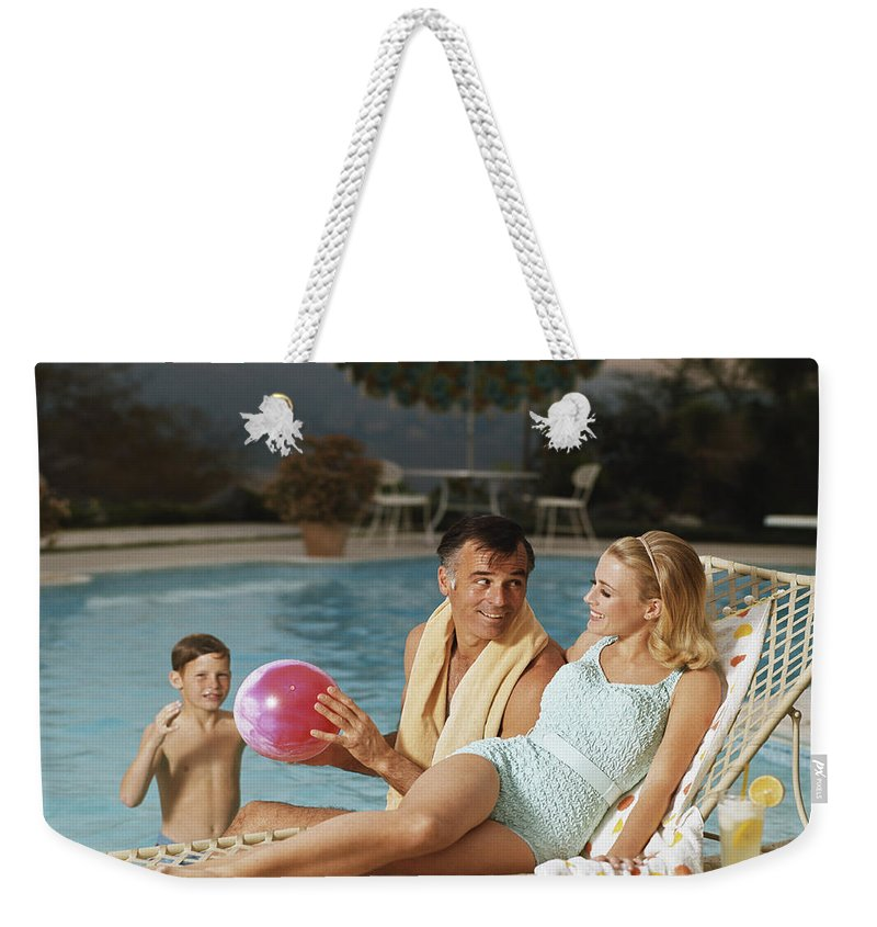 Mid Adult Women Weekender Tote Bag featuring the photograph Father And Son Playing With Beach Ball by Tom Kelley Archive