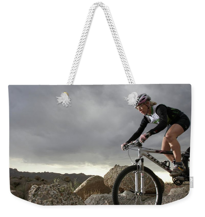 Sports Helmet Weekender Tote Bag featuring the photograph Female Rider Mountain Biking Between by Thomas Northcut