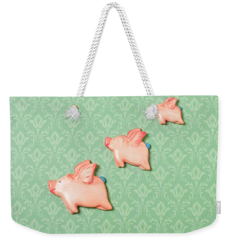 Disbelief Weekender Tote Bag featuring the photograph Flying Pig Ornaments On Wallpapered by Peter Dazeley
