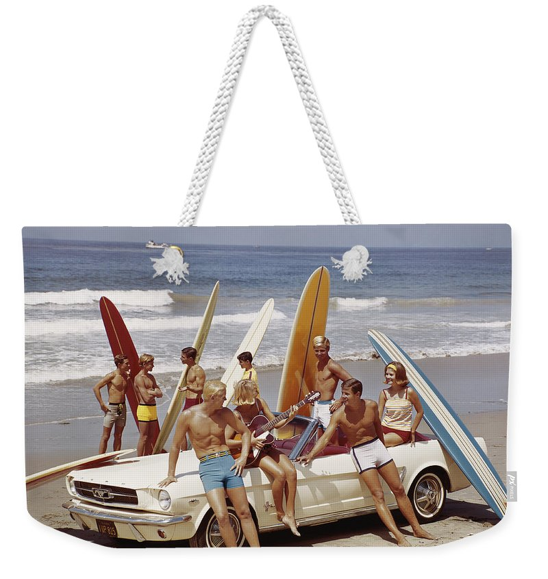 Young Men Weekender Tote Bag featuring the photograph Friends Having Fun On Beach by Tom Kelley Archive
