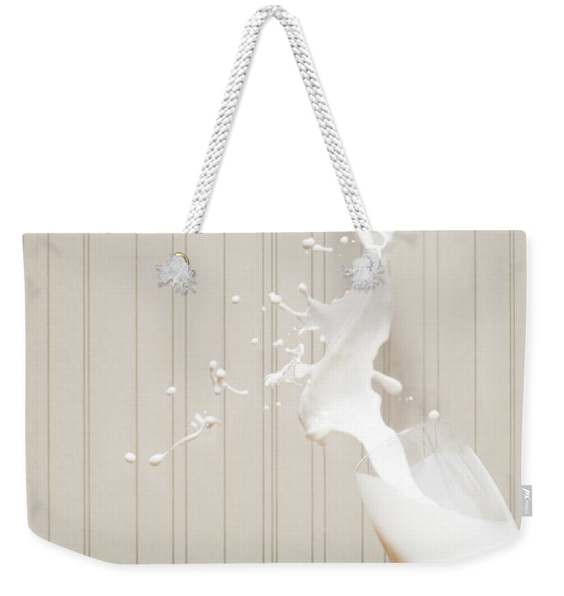 Milk Weekender Tote Bag featuring the photograph Glas Of Milk Spilling by Henrik Sorensen