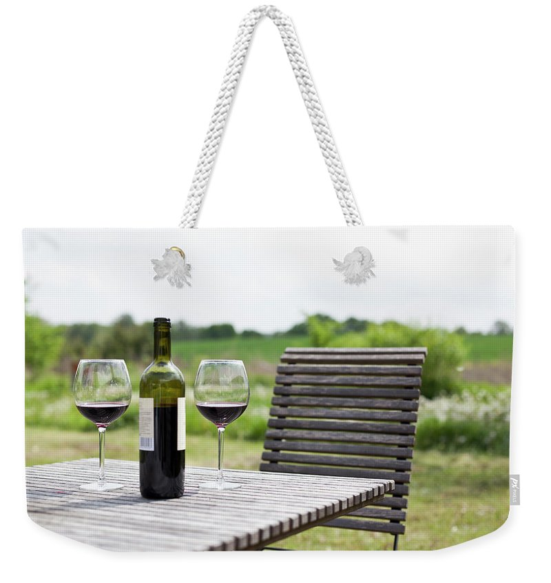 Five Objects Weekender Tote Bag featuring the photograph Glasses And A Bottle Of Red Wine On An by Halfdark