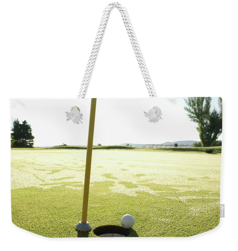 Grass Weekender Tote Bag featuring the photograph Golf Ball Near Hole At Sunrise, High by Ascent/pks Media Inc.