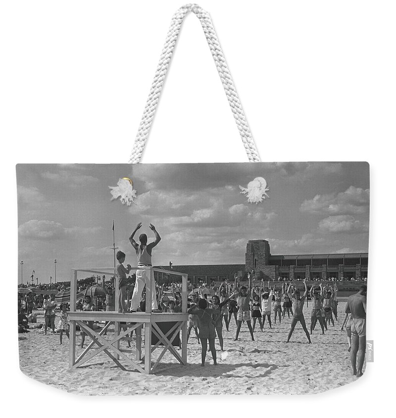 Human Arm Weekender Tote Bag featuring the photograph Group Of People Exercising On Beach, B&w by George Marks