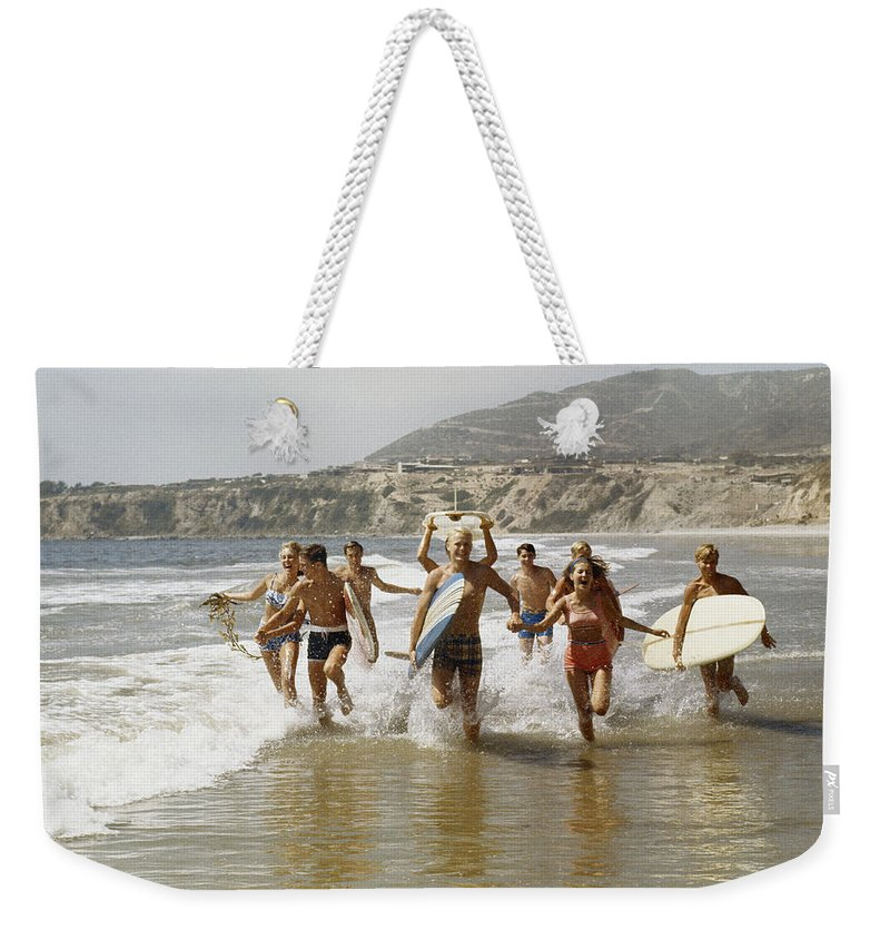 Young Men Weekender Tote Bag featuring the photograph Group Of Surfers Running In Water With by Tom Kelley Archive