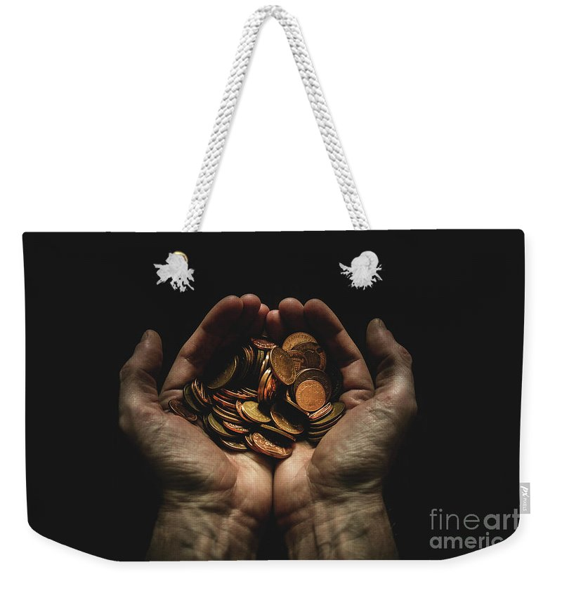 Coin Weekender Tote Bag featuring the photograph Hands Holding Coins Against Black by Andy Kirby