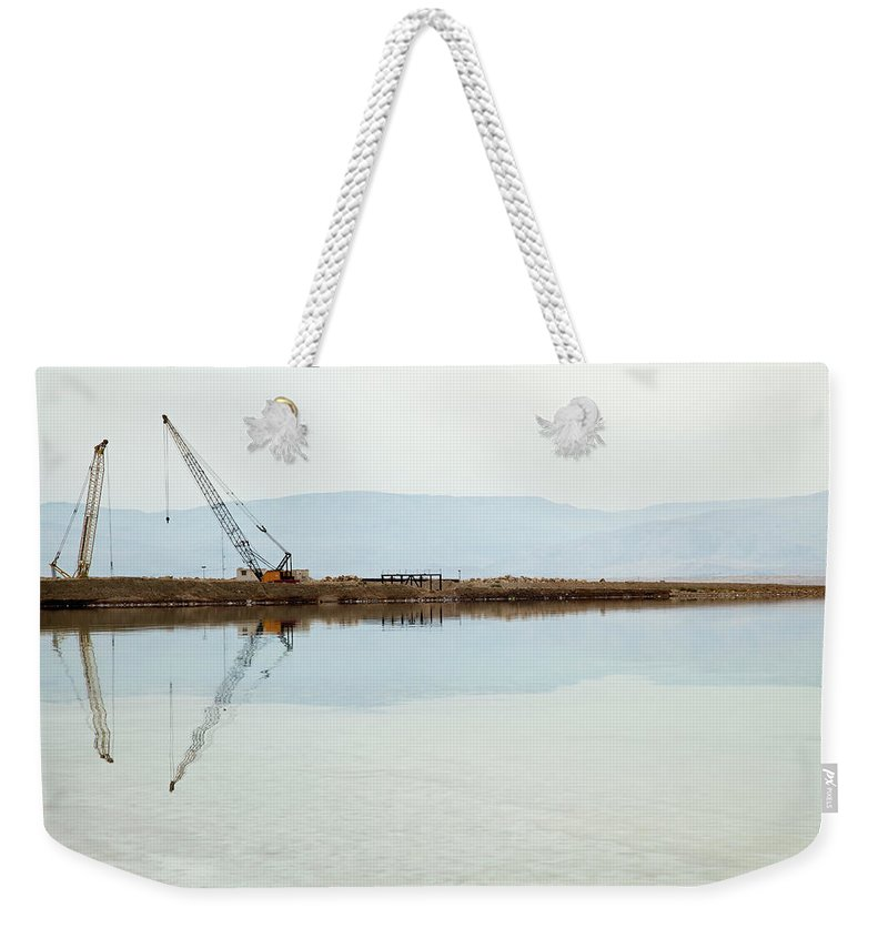 Working Weekender Tote Bag featuring the photograph Heavy Machinery At The Dead Sea by Eldadcarin