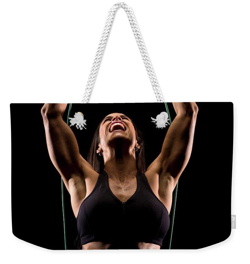 Resistance Band Weekender Tote Bag featuring the photograph Hispanic Woman Exercising by Juanmonino