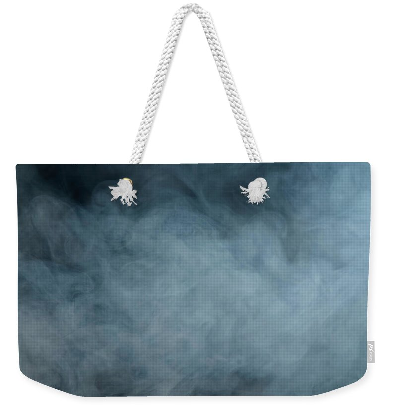 Air Pollution Weekender Tote Bag featuring the photograph Huge White Cloud Of Smoke In A Dark Room by Lastsax