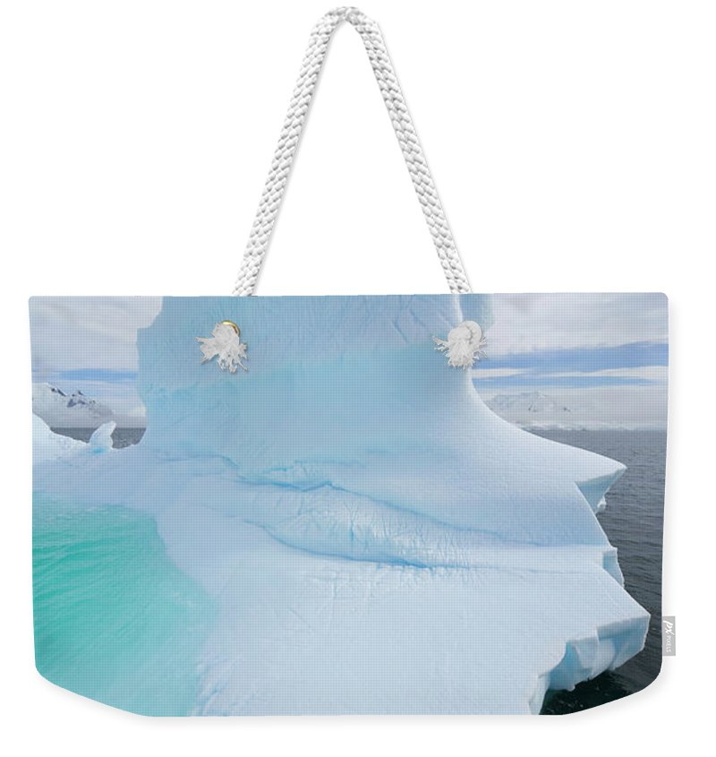 Scenics Weekender Tote Bag featuring the photograph Iceberg And Clouds, Antarctic Peninsula by Eastcott Momatiuk