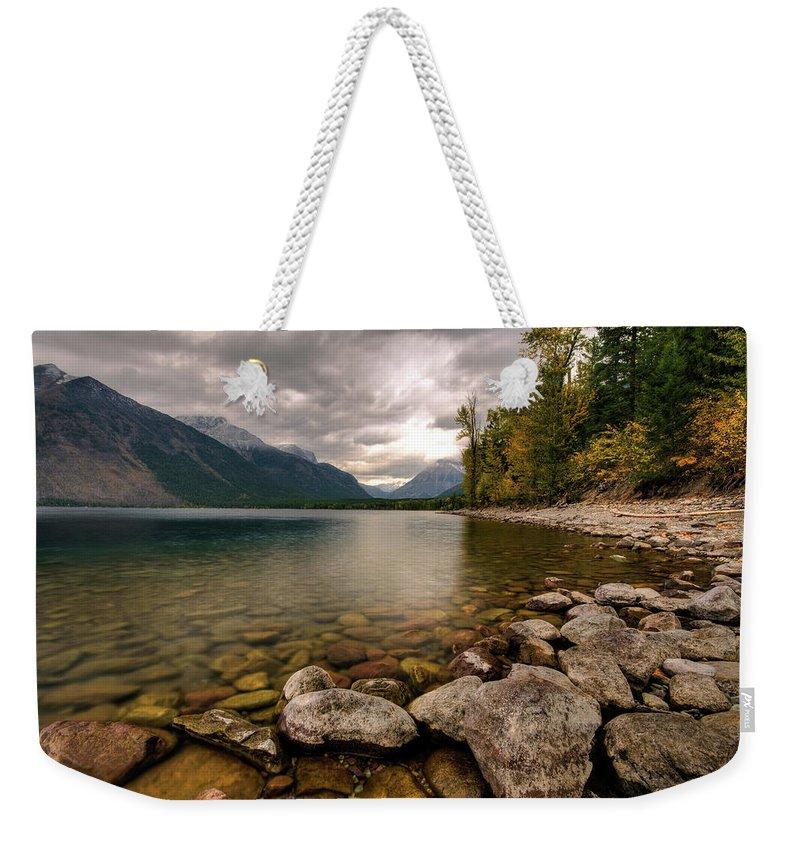 Water's Edge Weekender Tote Bag featuring the photograph Lake Mcdonald by Mason Cummings