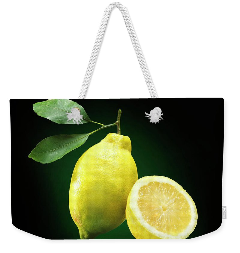 Black Background Weekender Tote Bag featuring the photograph Lemon Slice by Jeremy Hudson