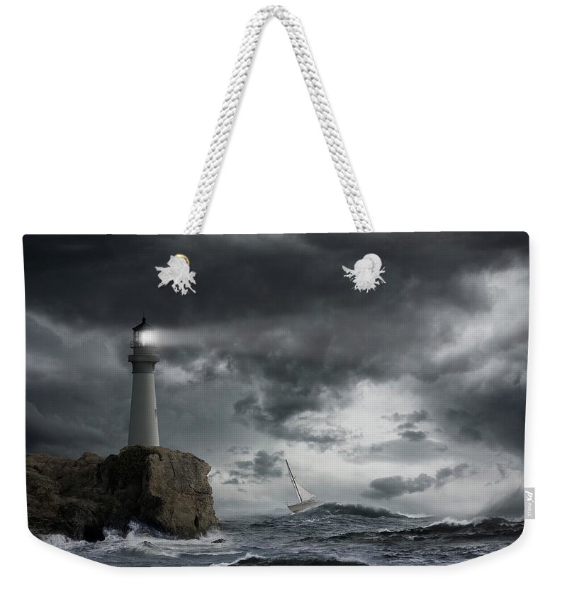 Risk Weekender Tote Bag featuring the photograph Lighthouse Shining Over Stormy Ocean by John M Lund Photography Inc