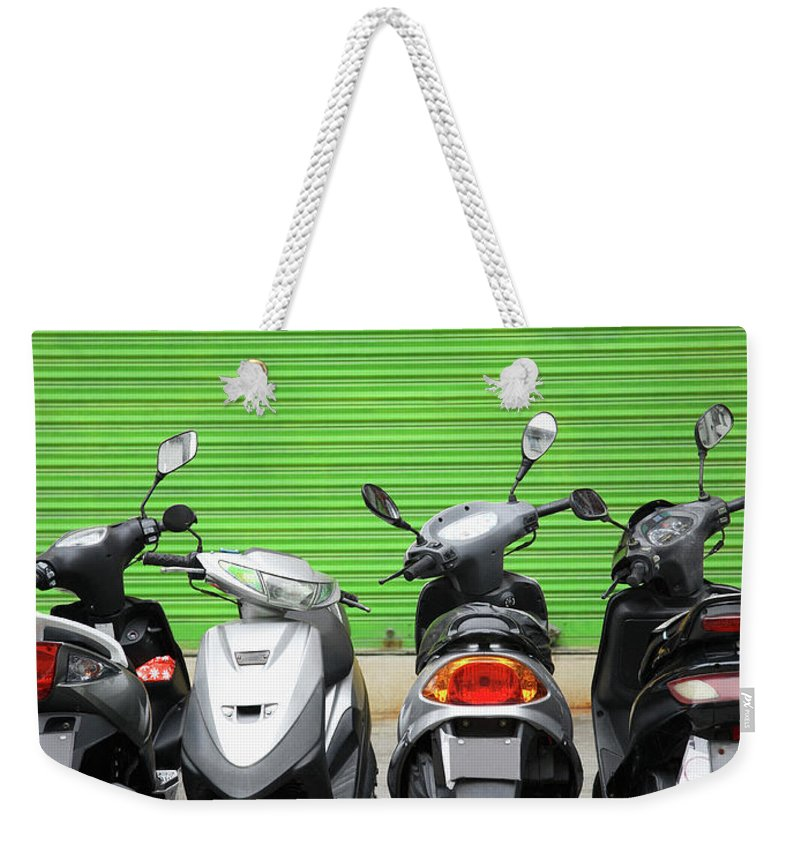 Macao Weekender Tote Bag featuring the photograph Line Of Motorbikes Against Green by Steven Puetzer