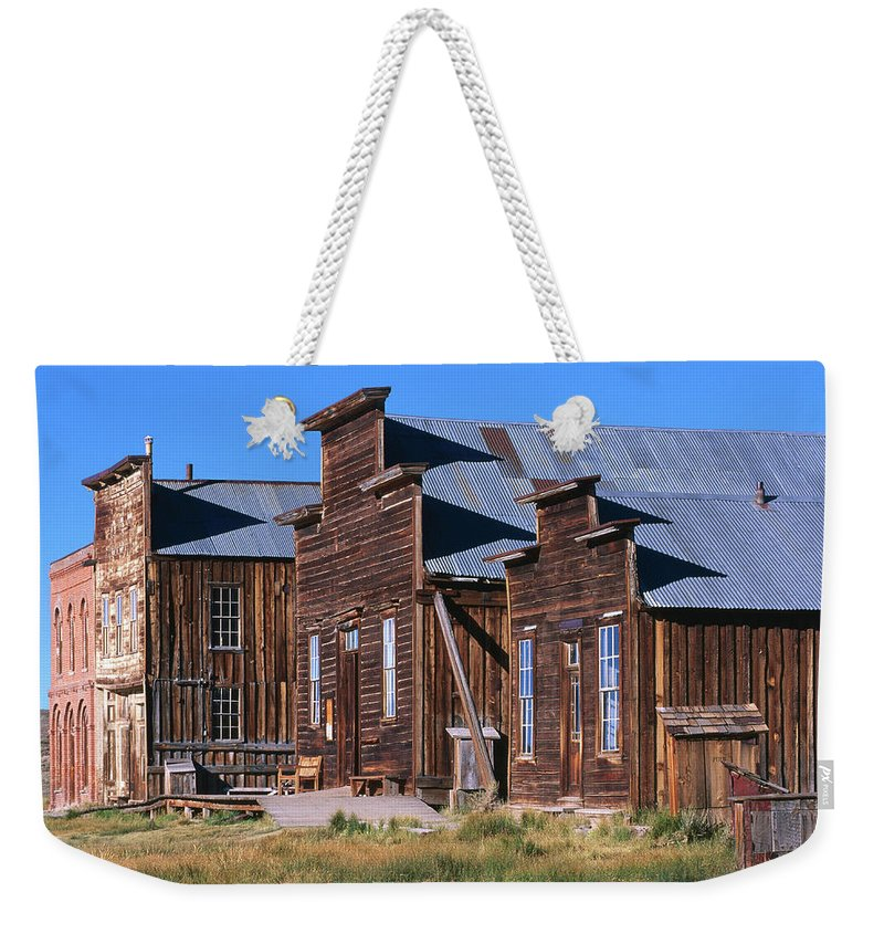 Grass Weekender Tote Bag featuring the photograph Main Street Buildings At Bodie Historic by John Elk Iii