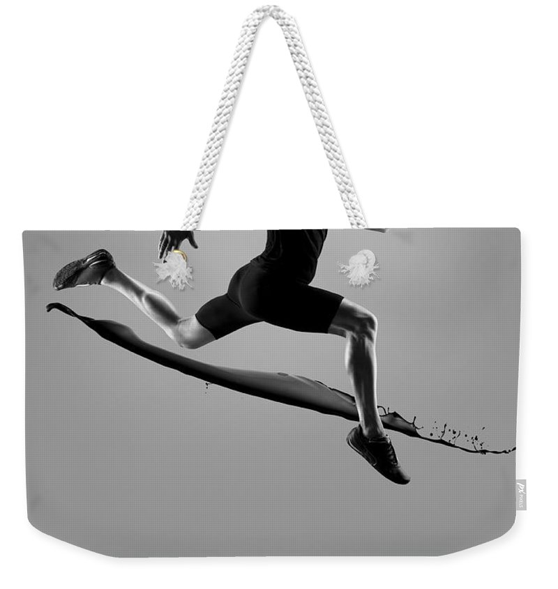 People Weekender Tote Bag featuring the photograph Male Athlete Running Above Liquid Splash by Jonathan Knowles
