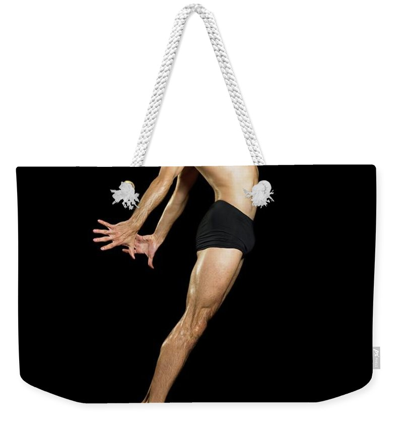 Human Arm Weekender Tote Bag featuring the photograph Male Dancer Jumping by Image Source