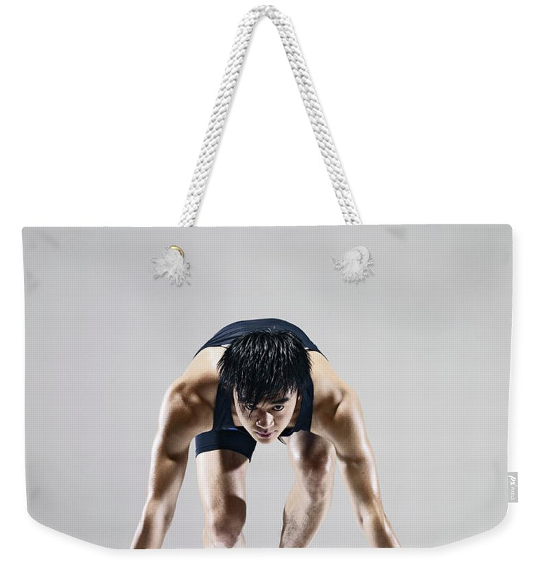 People Weekender Tote Bag featuring the photograph Male Runner In Starting Blocks by Ting Hoo