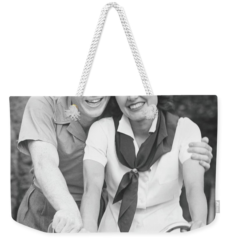 Young Men Weekender Tote Bag featuring the photograph Man Embracing Woman Sitting On Bike by George Marks