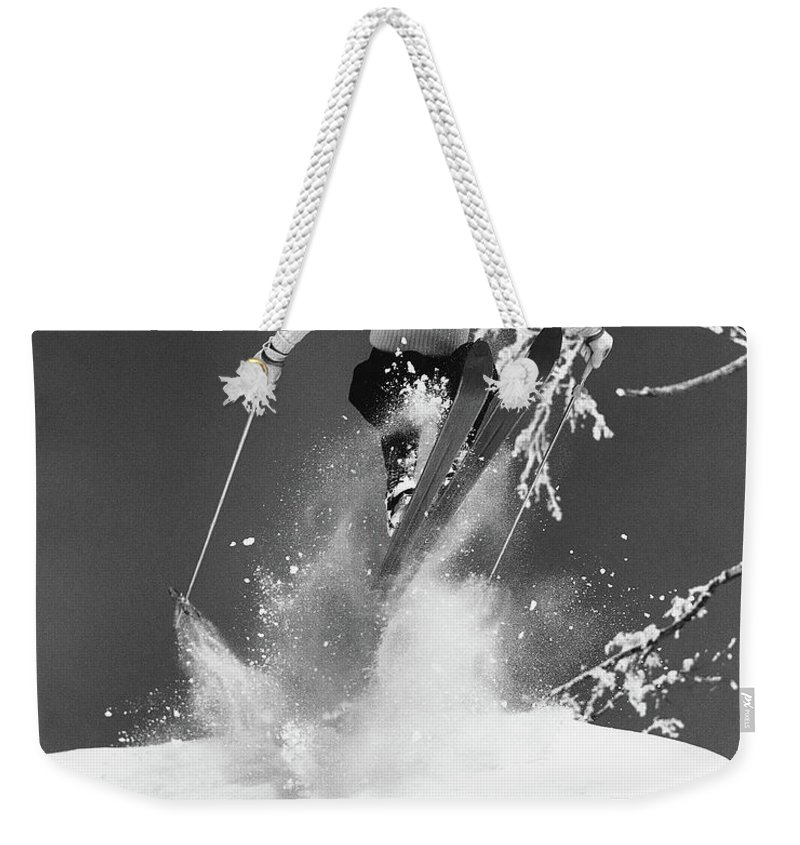 Skiing Weekender Tote Bag featuring the photograph Man Jumping Through Air On Skis by Stockbyte