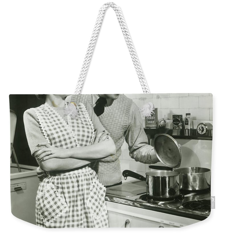 Heterosexual Couple Weekender Tote Bag featuring the photograph Man Looking Into Pot In Domestic by George Marks